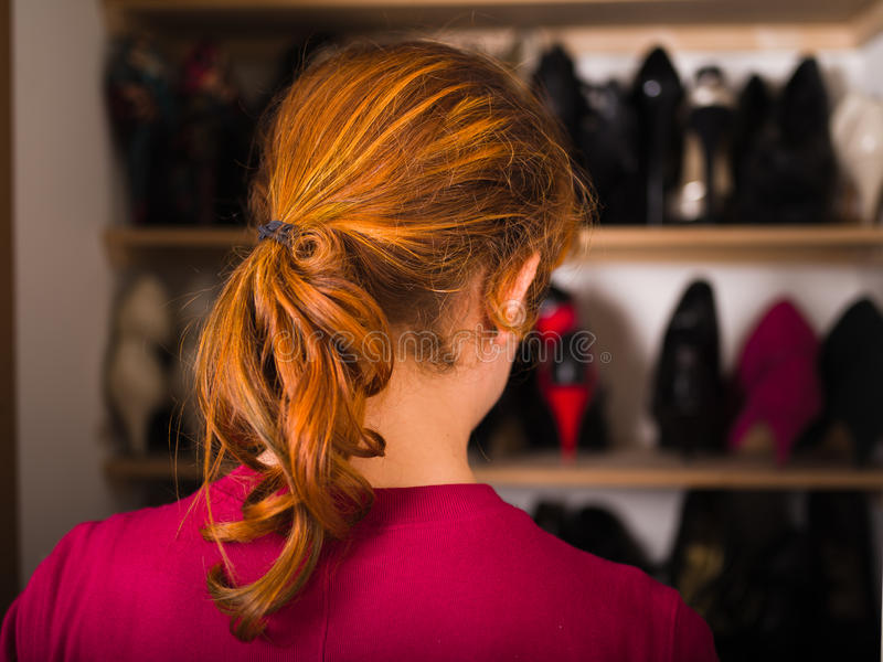 Woman organizing her shoes. A young woman is organizing her shoe cupboard at home stock images