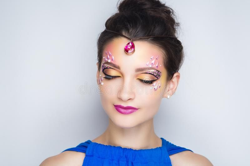 Woman oriental beauty. Oriental beauty girl. Portrait of a beautiful woman who wore bright accessory with pink stones and diamonds. Massive strap decorates her stock photography