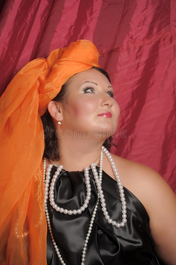 Woman in oriental clothes in an orange scarf stock photography