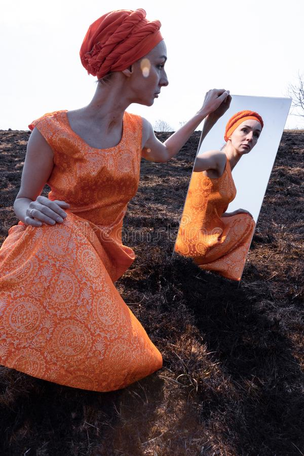 Woman in Eastern Clothes on Burnt Ground with Mirror royalty free stock photos