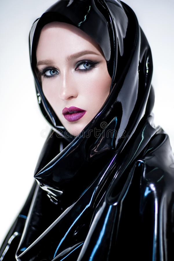 Woman with oriental makeup and black latex hijab stock photography