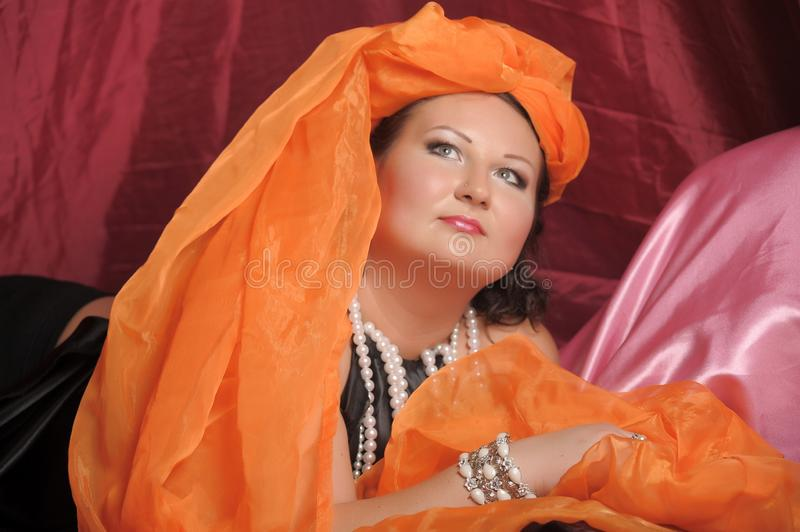 Woman in oriental robes is lazily laying on pillows royalty free stock photo