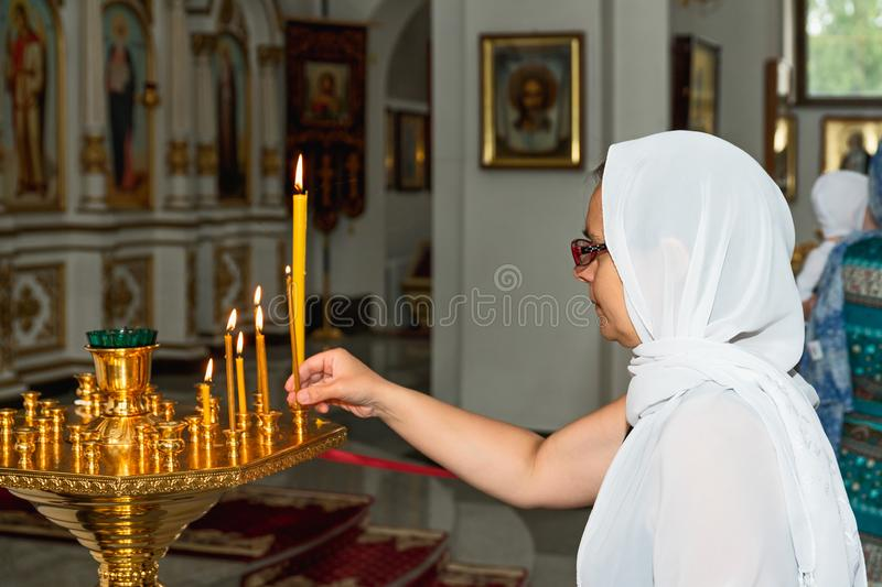 Woman in Orthodox Church. Woman with candle standing and praying in Orthodox Church. Belarus, Starobin, June 23, 2018 royalty free stock photo