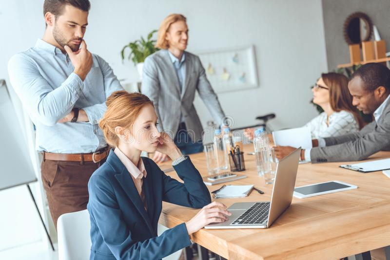woman and other businesspeople sitting at table and looking stock photo