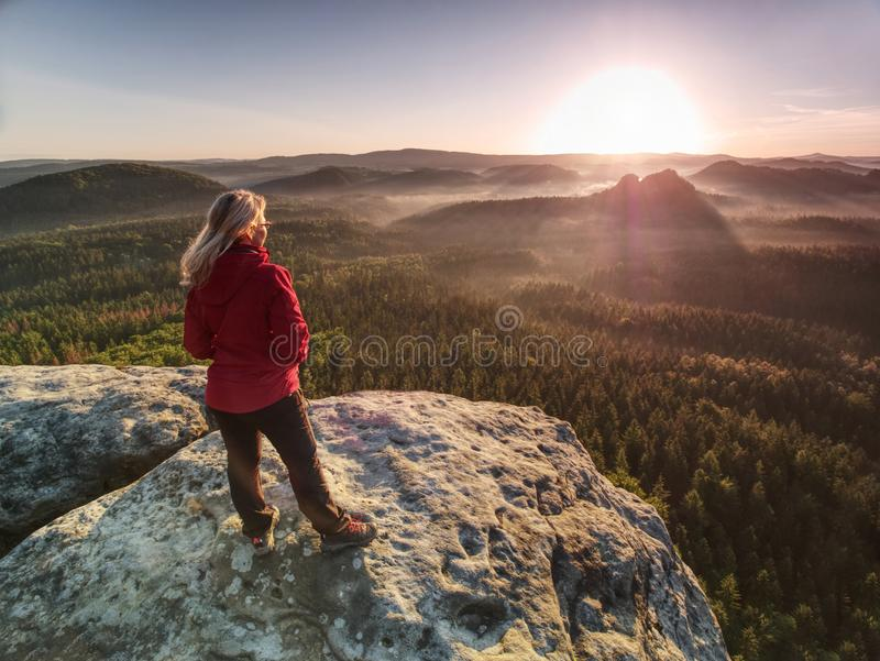 Woman in outdoor clothes  enjoy view at summit in mountains royalty free stock photos