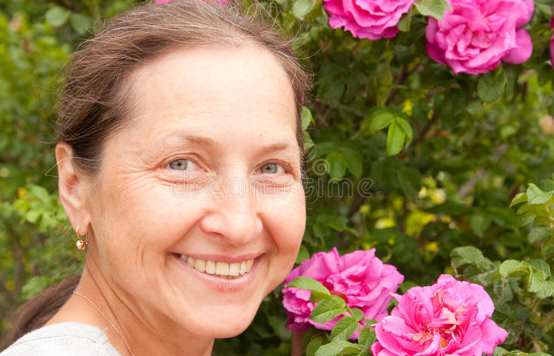 Woman outdoor near blossoming bush. Smiling adult woman with dogrose in her garden royalty free stock images