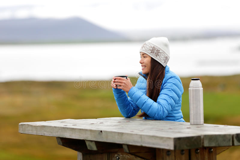 Woman in outdoors drinking coffee from thermos. Bottle flask sitting outside wearing warm down jacket and knit hat. Active young mixed race Asian Chinese stock photos