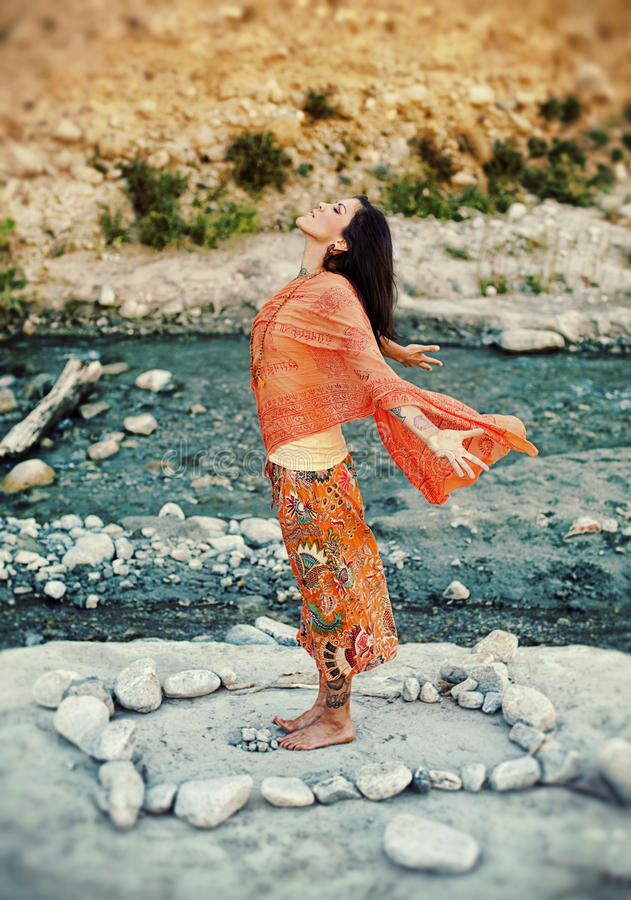 Heart Flowing Woman. Woman outdoors near a river with her arms and heart open in a mandala of stones