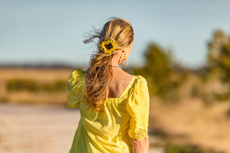 Woman outdoors in sunshine sunflower in her wavy hair stock photos