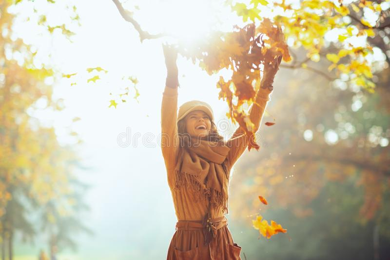 Woman outside in autumn park throwing up pile of yellow leaves royalty free stock photos