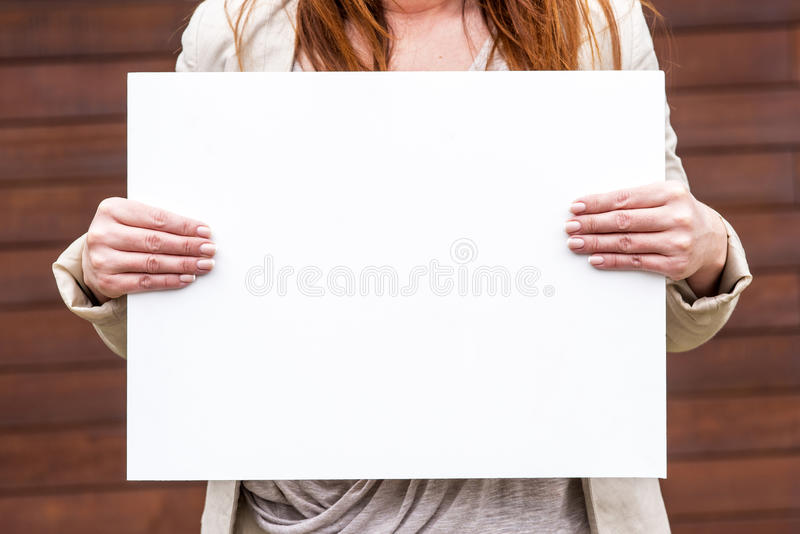 Woman outside with a blank white card. Photo of a woman on the outside with an empty white card royalty free stock image