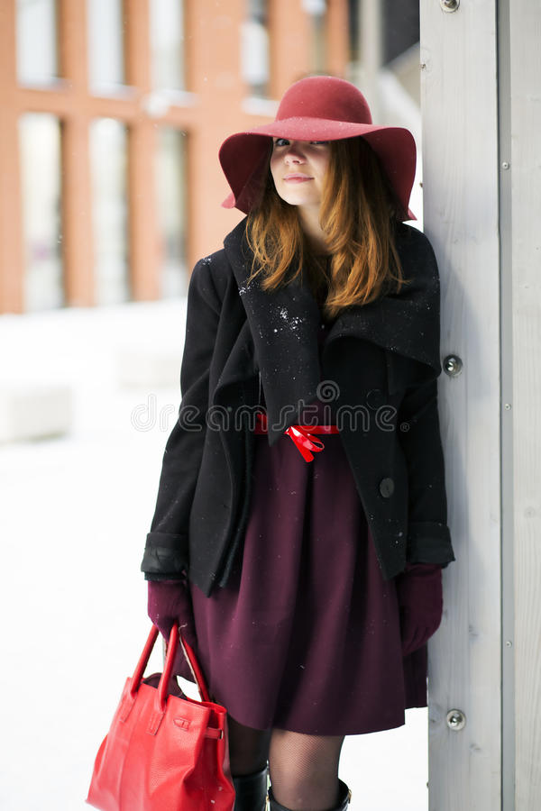 Woman outside door with big red purse. Smiling woman outside door with big red purse royalty free stock photo