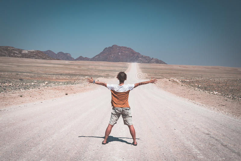 Woman with outstretched arms standing on gravel road crossing the Namib desert, in the Namib Naukluft National Park, main travel stock photos