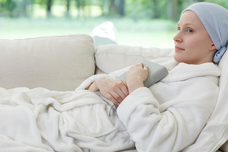 Woman with cancer on sofa stock photography