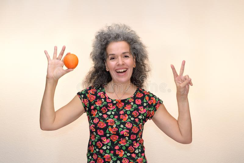 Smiling woman making V sign and holding orange. A woman over fifty is holding an orange in one hand and making a V sign with the other hand. Smiling, graying royalty free stock photography