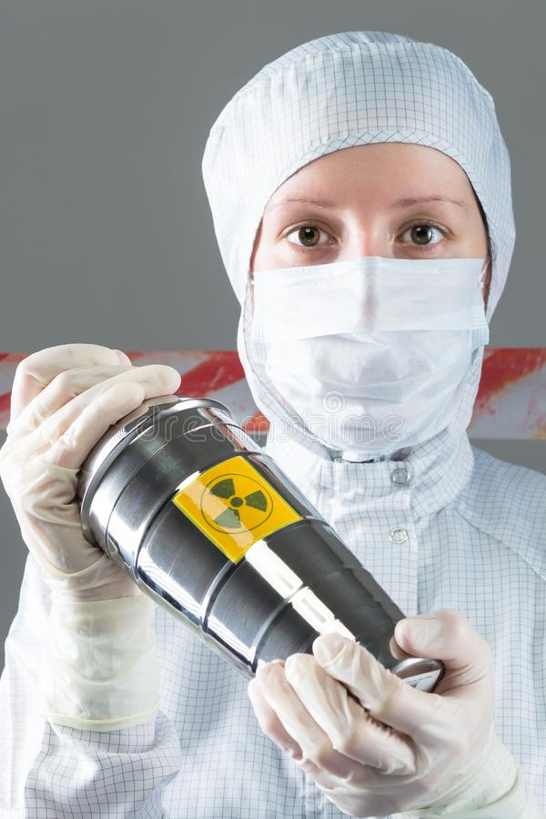 Woman in overalls is holding a container with radiation material stock image