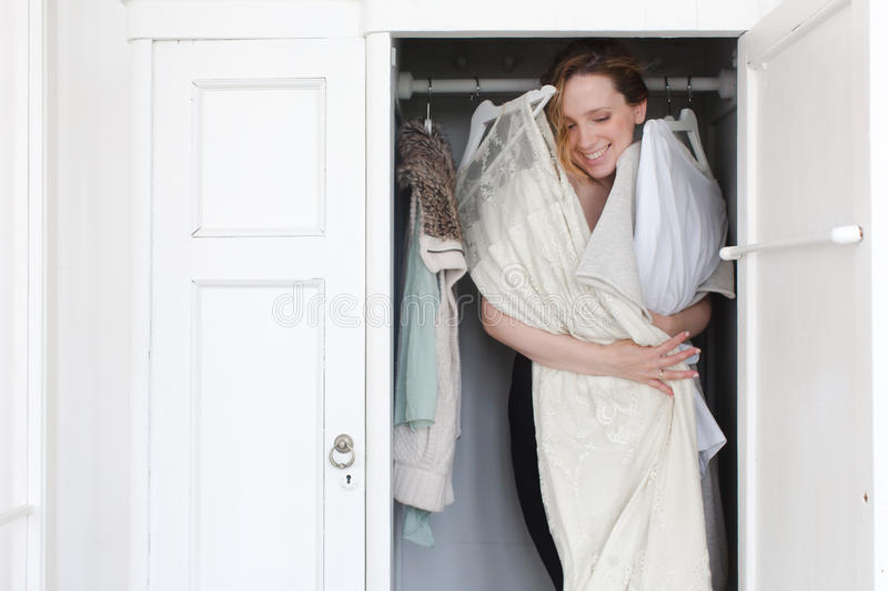 A woman is overwhelmed in closet of messy clothes. A woman is overwhelmed in a closet of messy clothes for a style or fashion concept stock photography