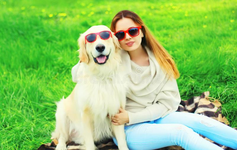 woman owner and Golden Retriever dog in sunglasses together on grass in summer royalty free stock images