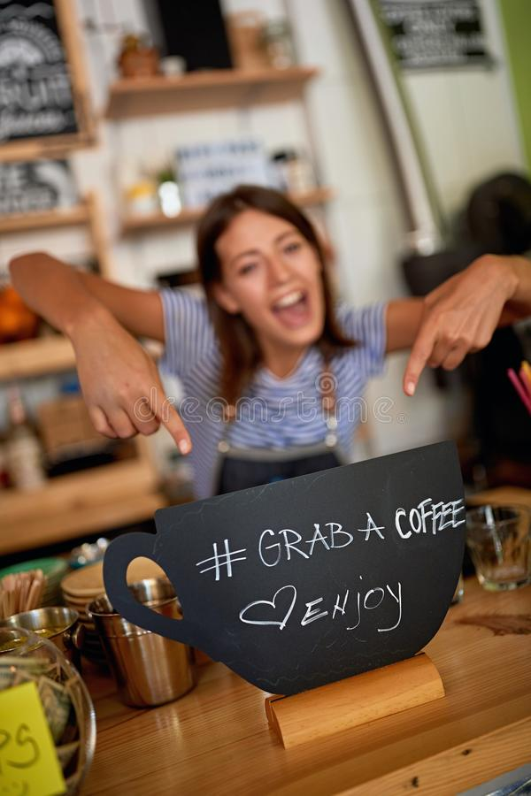 Woman owner with grab sign for coffee royalty free stock photo