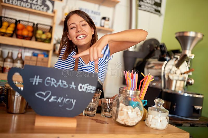Woman owner with sign for coffee stock images