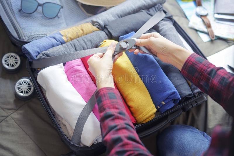 Woman pack clothes in suitcase bag on bed, prepare for new journey and travel to long weekend trip.  stock photo