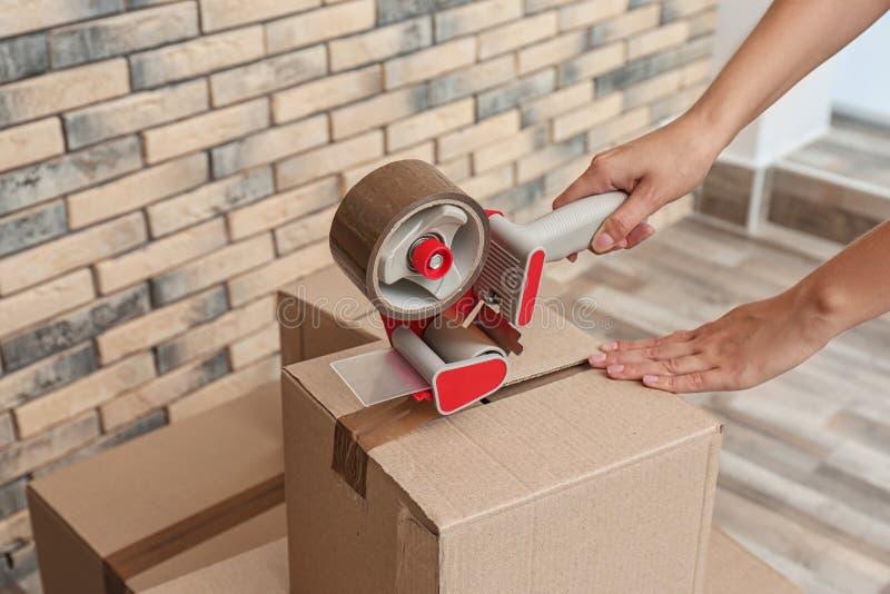 Woman packing carton box indoors, closeup stock photos