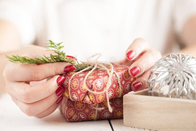 Woman is packing Christmas gifts. Red christmas gift boxes. royalty free stock photos