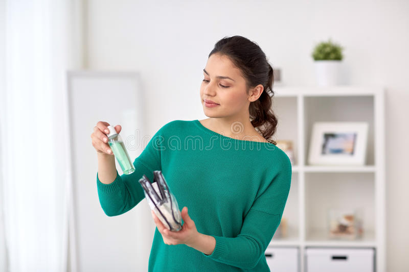 Woman packing cosmetics to cosmetic bag at home royalty free stock photo