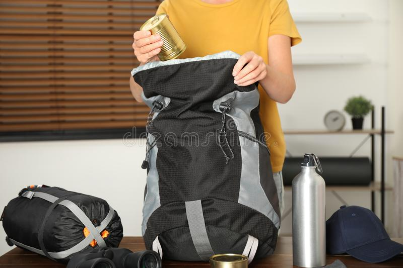 Woman packing different camping equipment into backpack at home. Closeup royalty free stock images