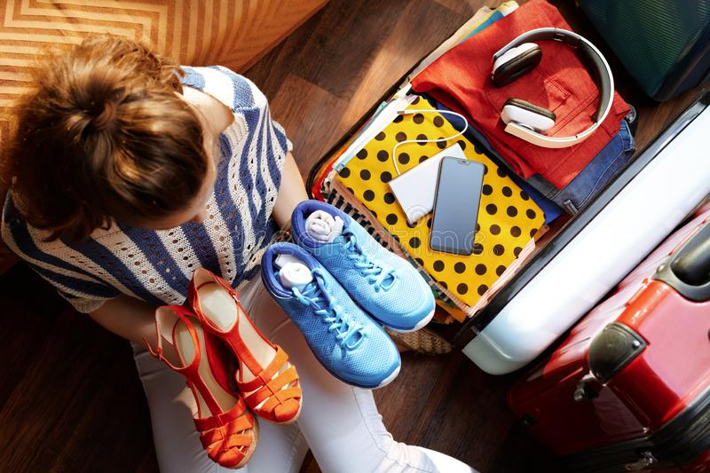 Woman packing fashion and comfortable shoes in travel suitcase royalty free stock photo