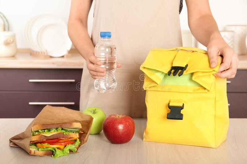 Woman packing food for her child at table stock images