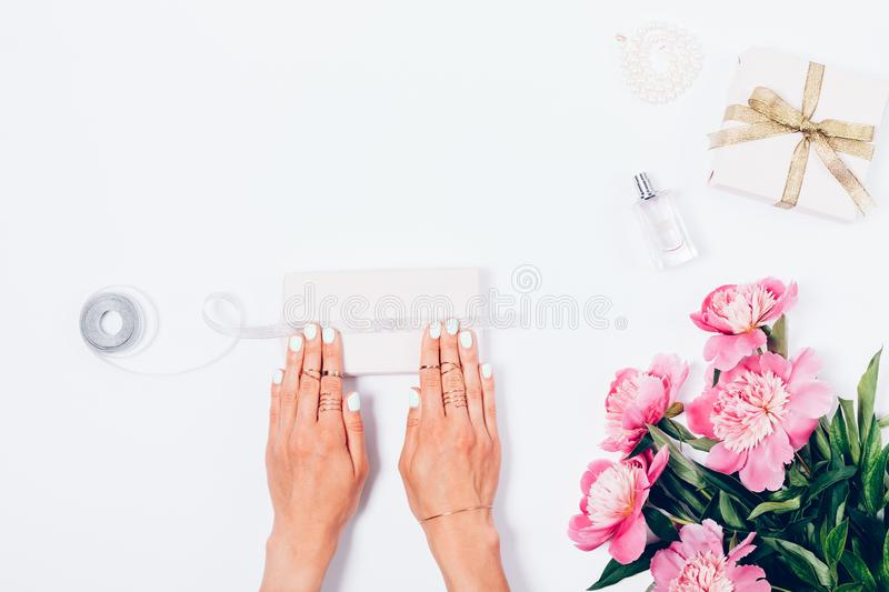Woman packing gifts next to pink peony flowers royalty free stock photography