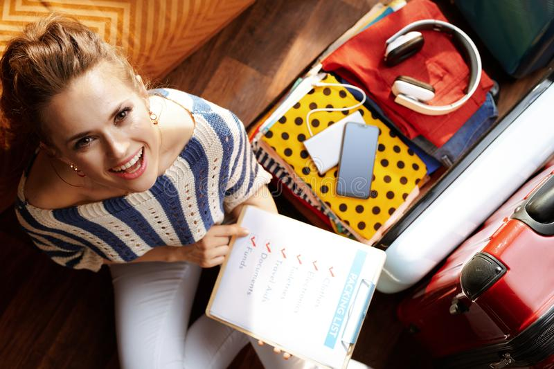 Woman with packing list at modern home in sunny summer day. Upper view of smiling young woman in white pants and striped blouse with packing list near open stock photo