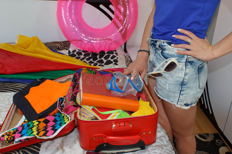 A woman packing a luggage for a new journey. Getting ready for travelling to the sea stock photography