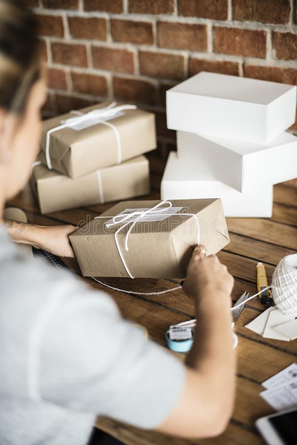 Woman packing parcels for shipping royalty free stock photo