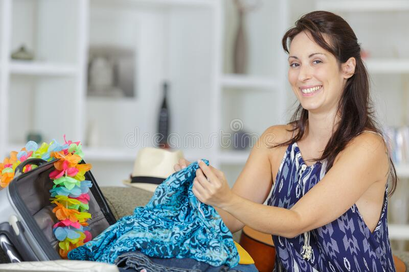 Woman packing suitcase at home stock photos