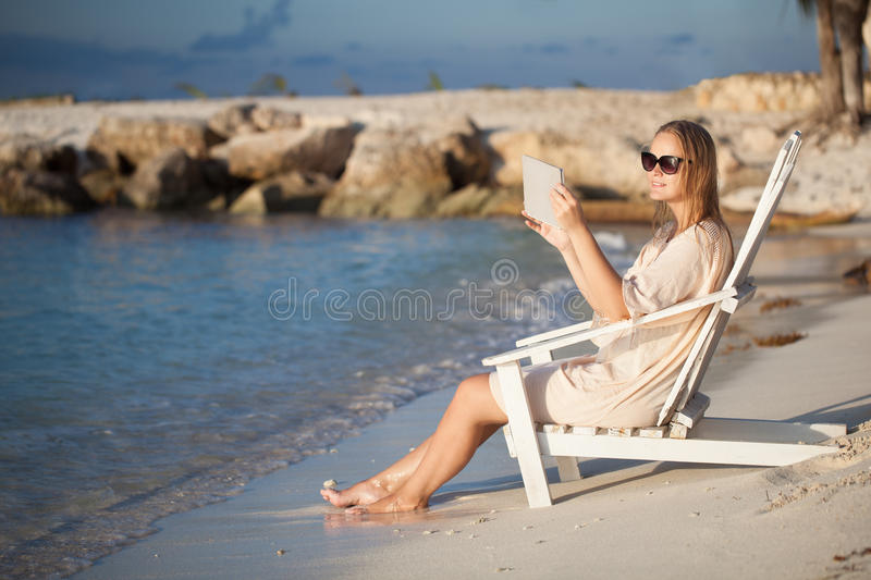 Woman with pad relaxing in chaise-lounge on the royalty free stock photos