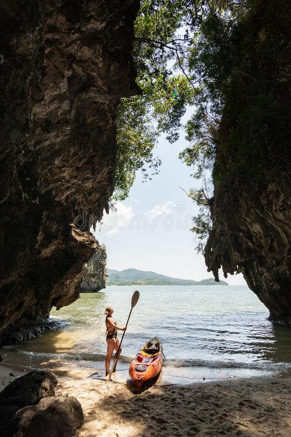 Woman with a paddle standing next to sea kayak at secluded beach in Krabi, Thailand stock photo