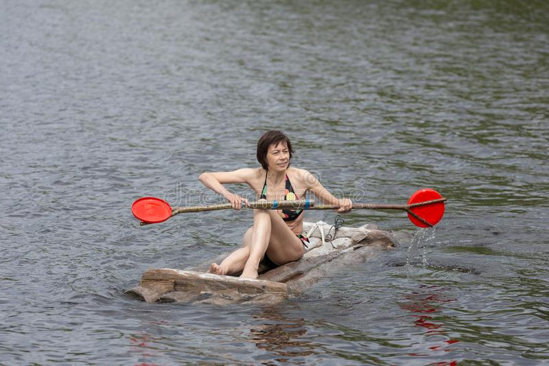 Woman with a paddle on a wooden raft royalty free stock photo
