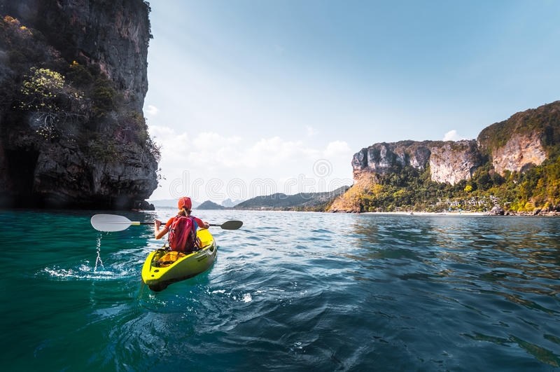 Woman paddles kayak royalty free stock photo