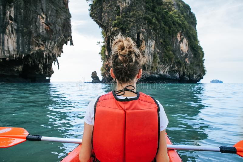 Woman paddles kayak in the lake with turquoise water. royalty free stock photography