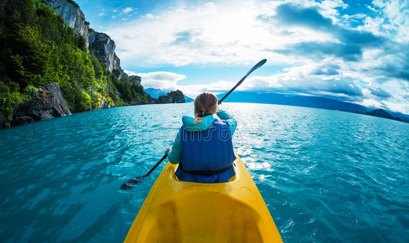 Woman paddles kayak in the lake with turquoise water royalty free stock image