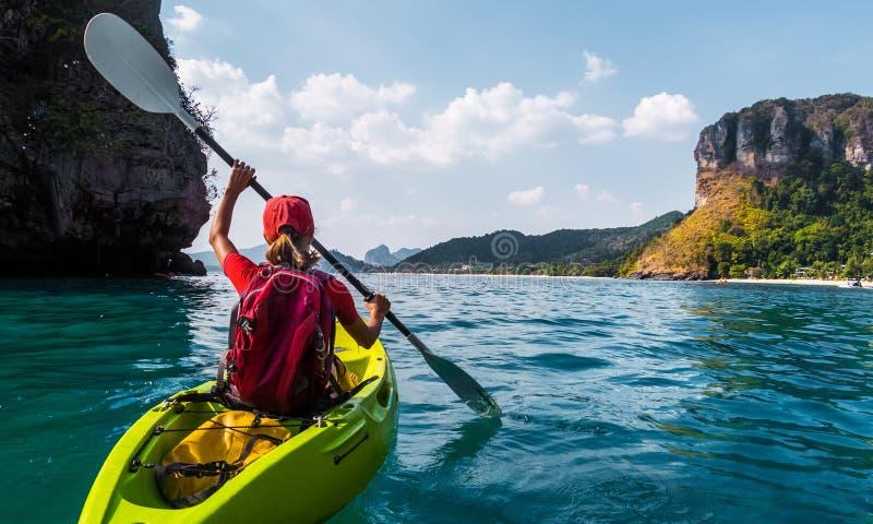 Woman paddles kayak stock photo