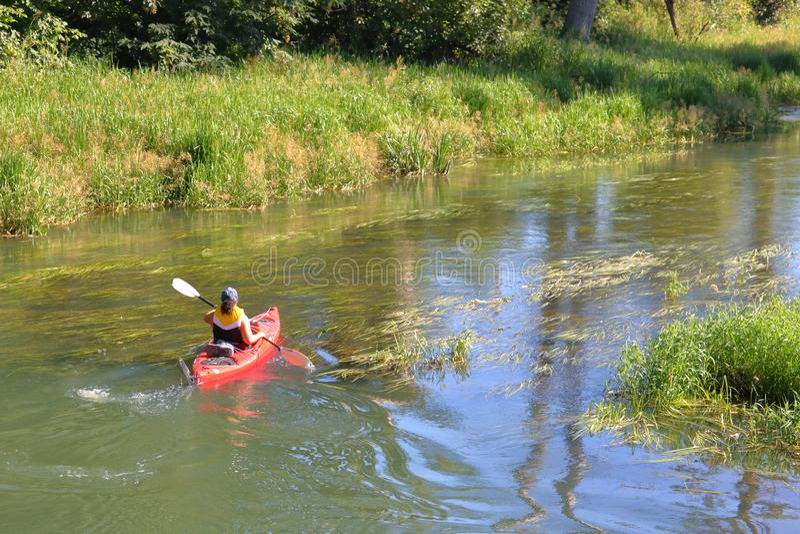 Woman Paddles Kayak on Winding Stream royalty free stock photos