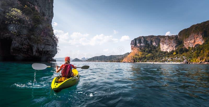 Woman paddles kayak stock images