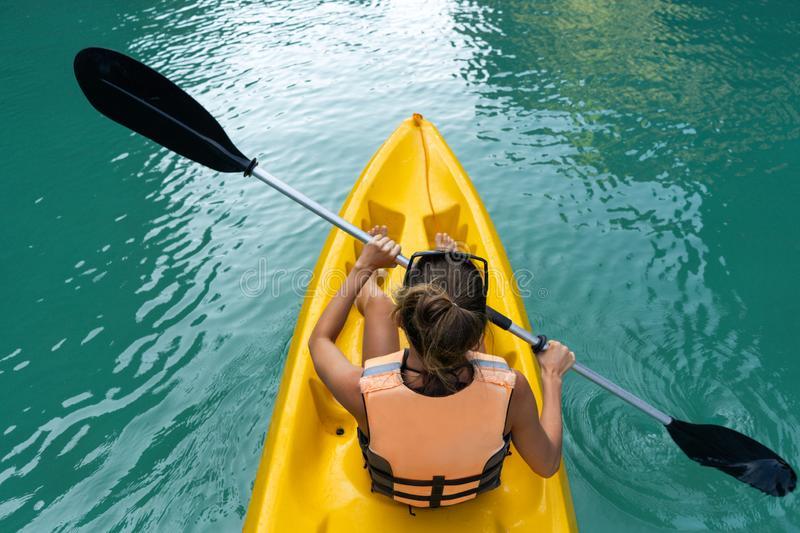 Woman paddles kayak in the lake with turquoise water royalty free stock photo
