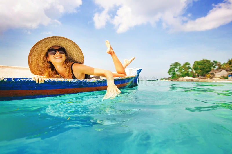 Woman paddling in a boat. In a paradise island royalty free stock image