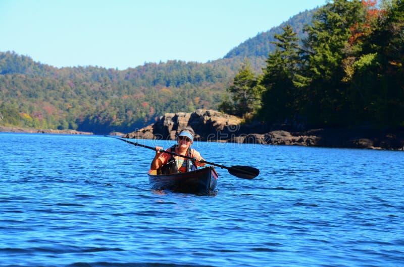 Woman paddling canoe on wilderness lake royalty free stock photography
