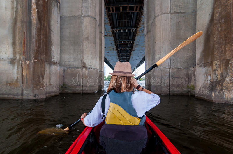 Woman paddling a kayak in the river between bridge supports. Kayaking in the city. Urban summer adventure concept royalty free stock photos