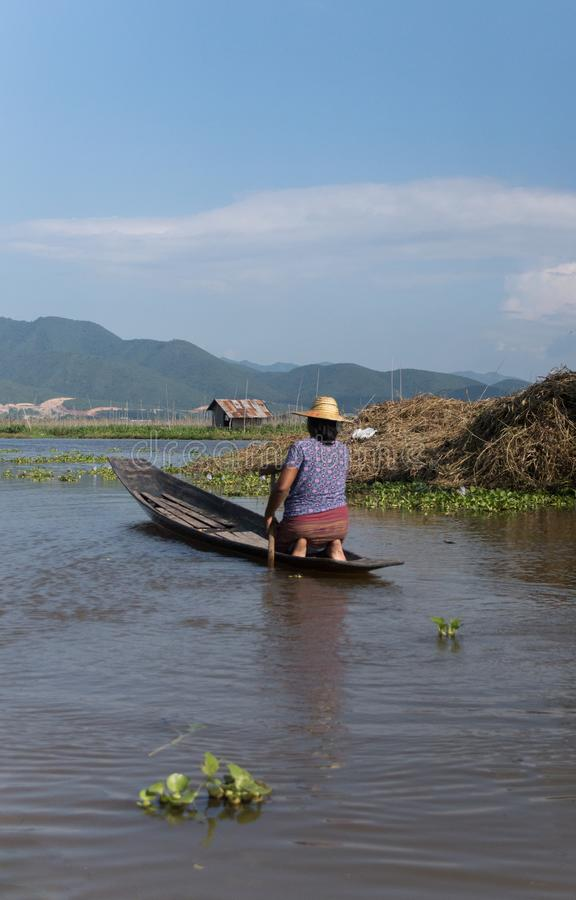 Woman paddling on a small wooden boat on inle lake in myanmar royalty free stock photo